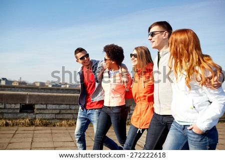 tourism, travel, people and leisure concept - group of happy teenage friends walking along city street and talking - stock photo