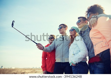 tourism, travel, people, leisure and technology concept - group of smiling teenage friends taking selfie with smartphone and monopod on city street - stock photo