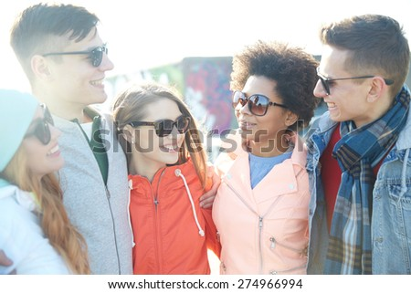 tourism, travel, people, leisure and teenage concept - group of happy friends in sunglasses hugging and talking on city street - stock photo