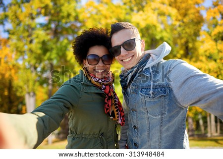 tourism, travel, people, season and technology concept - happy teenage international couple taking selfie over autumn park background - stock photo