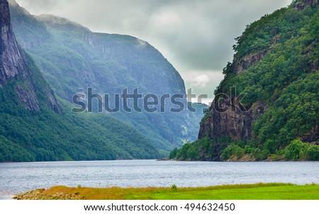 Tourism vacation and travel. Mountains landscape with stormy clouds and fjord in Norway Dalane region, Scandinavia.