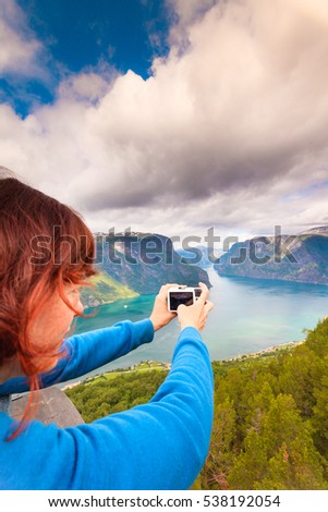 Tourism vacation and travel. Woman tourist taking photo with camera, enjoying Aurland fjord view from Stegastein viewpoint, Norway Scandinavia.