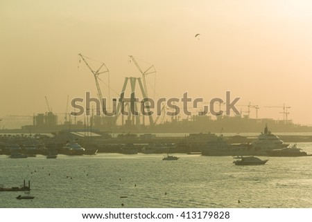 Tourism yachts docked near Jumeirah Beach with massive construction of buildings in the background and a parachutist in the sky, Dubai, United Arab Emirates - stock photo