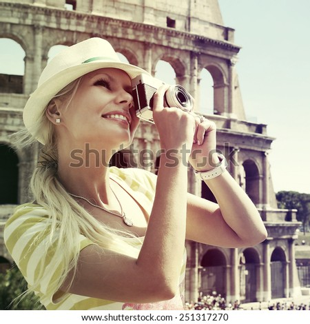 Tourist and Colosseum, Rome. Cheerful Young Blonde Woman with Camera in Italy. Travel in Europe - stock photo