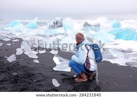 Tourist at ice rocks on the black sand beach in Iceland - stock photo