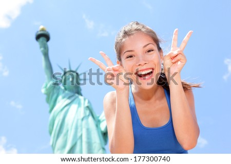 Tourist at Statue of Liberty, New York, USA making funny face expression victory hand signs excited and happy. Tourism and travel concept with joyful mixed race Asian Caucasian woman. - stock photo