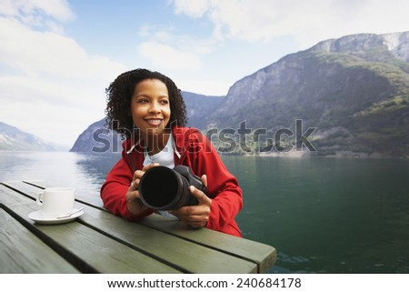 Tourist at Table Holding Camera - stock photo