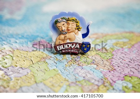 Tourist attractions and souvenir of Budva on a background map of the world of puzzles for travelers - stock photo
