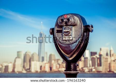 tourist binoculars at Liberty Island in front of Manhattan Skyline - stock photo