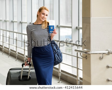 tourist blonde girl in a striped blouse standing on the station with a large suitcase and passport with tickets. - stock photo