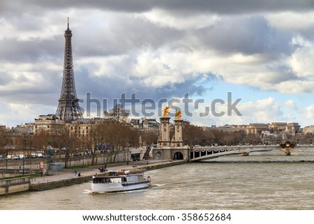 Tourist boat at the Seine in Paris with the Eiffel tower in the background on a cloudy winter day - stock photo