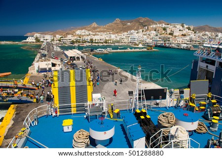 Tourist boat in the port of the island of Naxos, Greece. Loading and unloading of ship passengers. crowd of tourists in blur