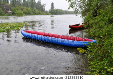 Tourist boat on the North taiga mountain river in the area of the Polar Urals. - stock photo