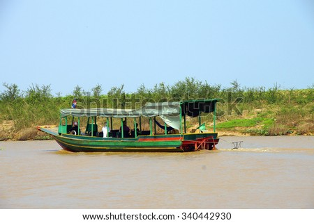 Tourist boat travels along the waterway of Kompong Kleang floating fishing village,  Cambodia - stock photo