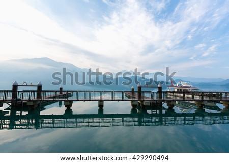 Tourist boats docking in peachful morning at Shuishe Pier, Sun Moon Lake, Taiwan. - stock photo