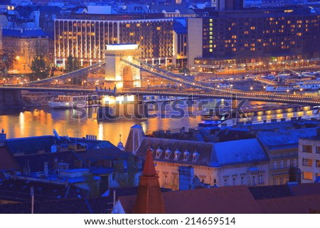 Tourist boats on Danube river and buildings and bridge illuminated by night, Budapest, Hungary