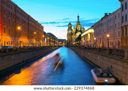 Tourist boats sail to the Church of Savior on Spilled Blood at White Night in St Petersburg, Russia. This is an architectural landmark of central St Petersburg, and a unique monument to Alexander II. - stock photo