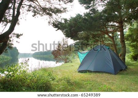 Tourist camping in the wilderness at the river - stock photo