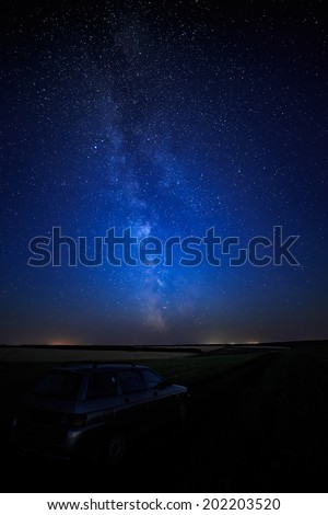 Tourist car on a starry background sky and the Milky Way.  - stock photo