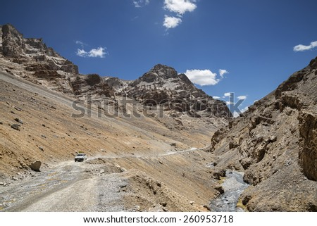Tourist car on high mountains road - stock photo
