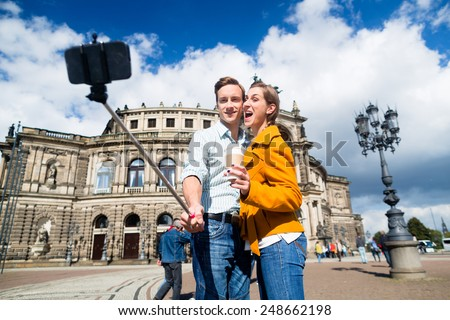 Tourist couple at Semperoper in Dresden taking selfie with phone on stick - stock photo