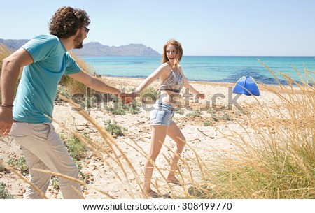 Tourist couple having fun with woman taking man by the hand, running towards the sea, enjoying a summer holiday together on a camping beach exterior. Travel and lifestyle vacation, nature exterior. - stock photo
