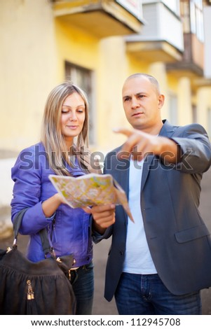 tourist couple looking at the map in the city - stock photo