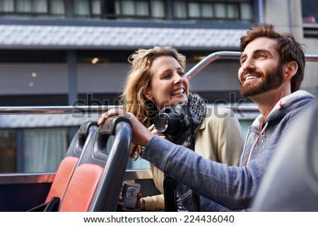 tourist couple on open top bus tour guide around the city in vacation - stock photo