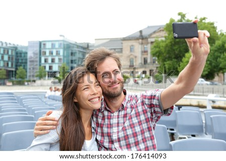 Tourist couple on travel in Berlin, Germany on boat tour cruise smiling happy taking selfie self-portrait photo picture while enjoying their romantic Europe travel vacation. Asian woman, Caucasian man