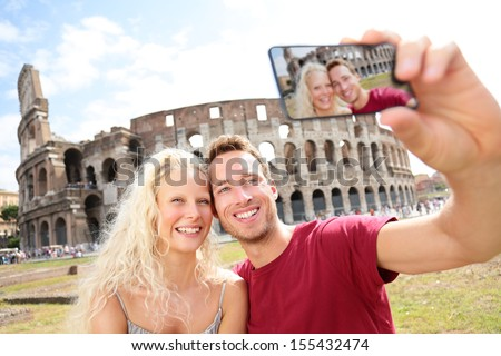 Tourist couple on travel taking pictures by Coliseum in Rome. Happy young romantic couple traveling in Italy, Europe taking self-portrait with smartphone camera in front of Colosseum. Man and woman. - stock photo