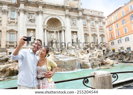 Tourist couple on travel taking selfie photo by Trevi Fountain in Rome, Italy. Happy young romantic couple traveling in Europe taking self-portrait with smartphone camera. Man and woman happy together - stock photo