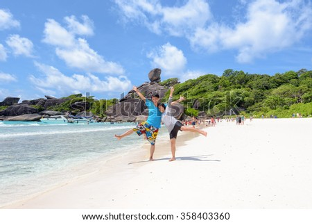 Tourist couple raised his arms and legs with happy on beach near the sea under blue sky and cloud of summer at Koh Similan Island in Mu Ko Similan National Park, Phang Nga province, Thailand - stock photo