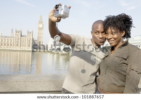 Tourist couple taking a picture of themselves while visiting Big Ben in London city.