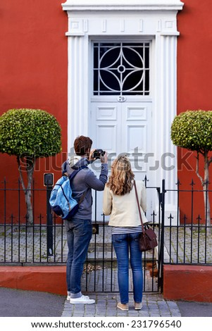 tourist couple taking photo of interesting building while walking around new city - stock photo