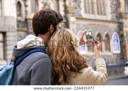tourist couple taking photo of old historical church on holiday