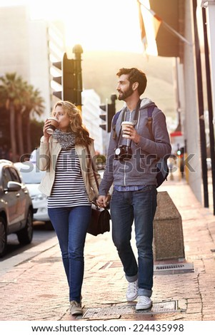 tourist couple travel with coffee ab camera walk through city having fun