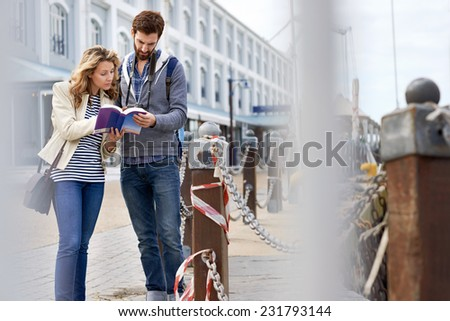 tourist couple with guide book on vacation - stock photo