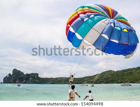 Tourist ejoy parachuting in the sea. - stock photo