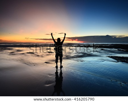 Tourist Enjoying Majestic Sunset With Raised Both Hands At Beach,Bali,Indonesia. - stock photo