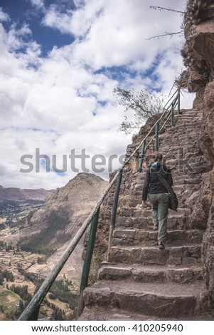 Tourist exploring the majestic steep Inca Trails inside the ruins of Pisac, Sacred Valley, major travel destination in Cusco region, Peru. Expansive view from above, Desaturated image. - stock photo
