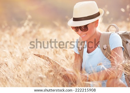 Tourist girl exploring map, active beautiful female searching right direction on the map, sitting in dry wheat field, autumn travel concept - stock photo