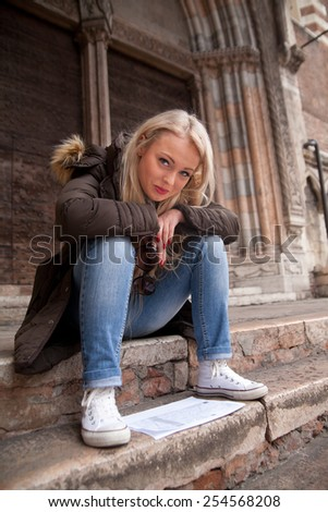 tourist girl reading directions on a map on stairs - stock photo