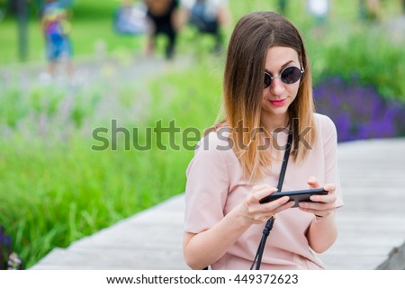 Tourist girl sending messgae by smartphone on summer holidays. Young attractive woman with mobile phone outdoors enjoying holidays travel destination in tourism and exploring concept