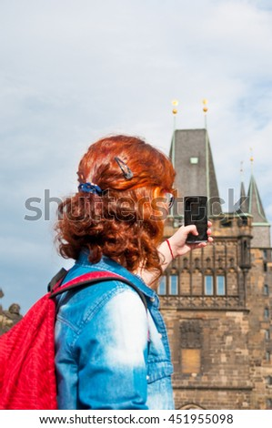 Tourist girl taking a picture of Prague city