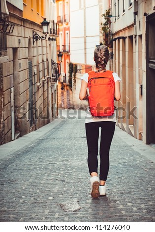 Tourist girl with backpack is walking by the street