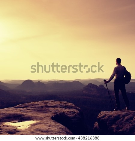 Tourist guide on cliff edge with pole in hand. Hiker with sporty backpack stand on rocky view point above misty valley. Sunny spring daybreak in rocky mountains. - stock photo