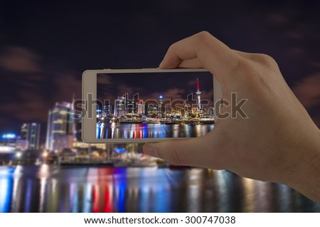 Tourist hand holding smart phone, taking photo of Auckland New Zealand, Devonport - stock photo
