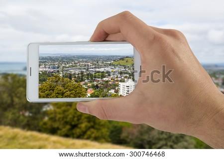 Tourist hand holding smart phone, taking photo of Auckland New Zealand, Mount Eden Volcano - stock photo