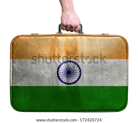 Tourist hand holding vintage leather travel bag with flag of India - stock photo