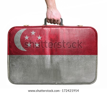 Tourist hand holding vintage leather travel bag with flag of Singapore - stock photo
